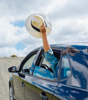 mulher segurando chapéu pela janela representando como planejar uma viagem